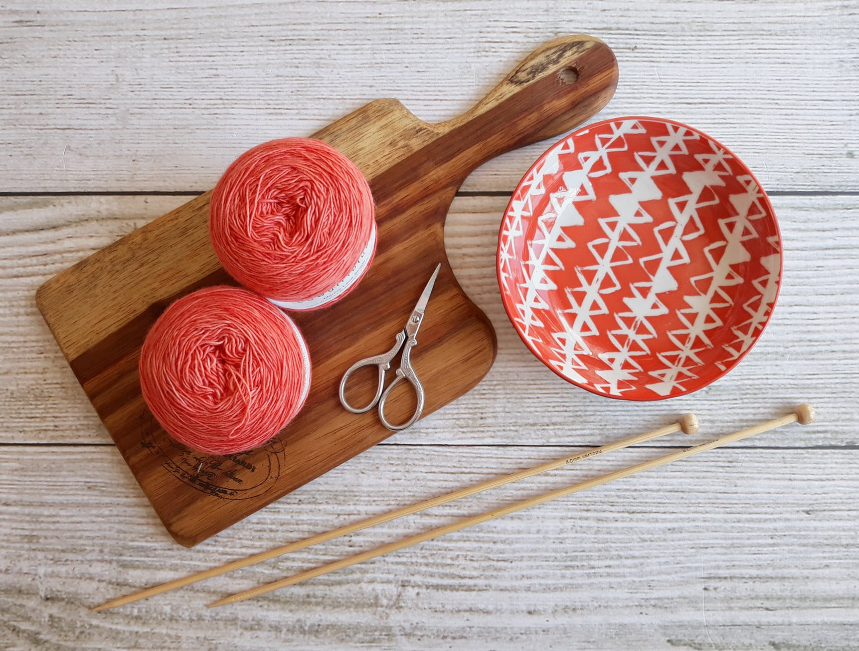 two pink spools on brown wooden chopping board beside orange bowl